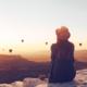 woman looking at hot air balloons